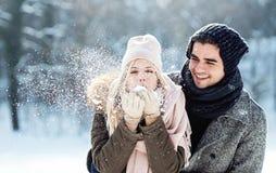 Due giovani che godono nella neve immagini stock