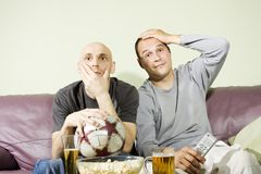 Due giovani che guardano una partita di gioco del calcio sulla TV Fotografia Stock