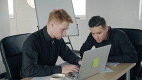 Due giovani che lavorano facendo uso del computer portatile in posto di lavoro in ufficio moderno video d archivio