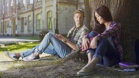 Due giovani che si siedono sotto l'albero, ragazza che guardano giù e tipo che la esamina Immagini Stock Libere da Diritti