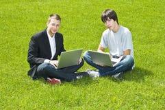 Due giovani che si siedono sull'erba con i loro computer portatili Immagine Stock Libera da Diritti
