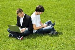 Due giovani che si siedono sull'erba con i loro computer portatili Fotografie Stock