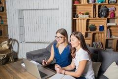 Due giovani colleghe che hanno collaborazione, guardare webinar in Internet sul computer portatile Immagine Stock