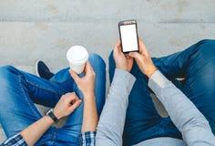 Due giovani con il telefono a disposizione Immagine Stock