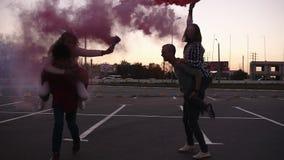 Due giovani coppie con le bombe fumogene in mani sulla zona di parcheggio vuota fuori Amici - gli uomini e le donne stanno giocan archivi video
