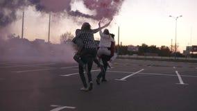 Due giovani coppie pazze con le bombe fumogene variopinte in mani sulla zona di parcheggio vuota fuori Amici - uomini e donne stock footage