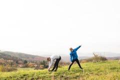 Due giovani corridori dei pantaloni a vita bassa in natura soleggiata di autunno che allunga le gambe Immagini Stock