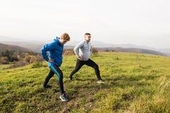 Due giovani corridori dei pantaloni a vita bassa in natura soleggiata di autunno che allunga le gambe Fotografia Stock
