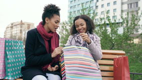 Due giovani donne afroamericane che dividono i loro nuovi acquisti nello shoppping insacca a vicenda Conversazione attraente dell video d archivio