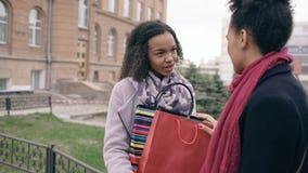 Due giovani donne afroamericane che dividono i loro nuovi acquisti nello shoppping insacca a vicenda Conversazione attraente dell stock footage