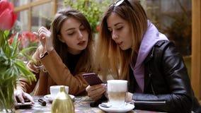 Due giovani donne attraenti in abbigliamento casual - rilassandosi ed avere conversazione nella caffetteria della via Uno che div archivi video