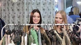 Due giovani donne attraenti che scelgono i vestiti nel deposito archivi video