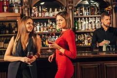 Due giovani donne attraenti che si trovano in un pub per vetro di vino rosso che si siede al contatore che si sorride Immagini Stock