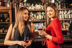 Due giovani donne attraenti che si trovano in un pub per vetro di vino rosso che si siede al contatore che si sorride Fotografia Stock