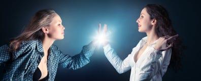 Due giovani donne che allungano le mani immagine stock