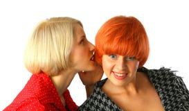 Due giovani donne che bisbigliano e sorprese Fotografia Stock