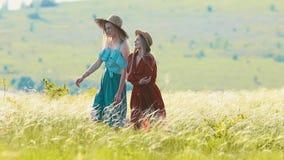 Due giovani donne che camminano sul campo nel giorno soleggiato stock footage