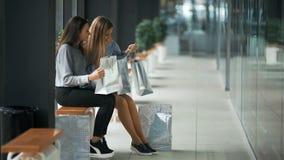 Due giovani donne che dividono i loro nuovi acquisti a vicenda video d archivio