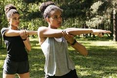 Due giovani donne che fanno allungando gli esercizi Immagine Stock Libera da Diritti