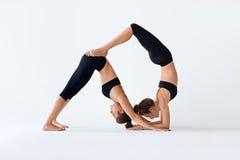 Due giovani donne che fanno il asana di yoga del partner giù inseguono e scorpione Immagine Stock