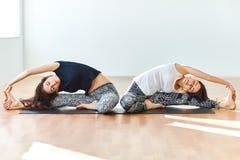Due giovani donne che fanno il asana di yoga hanno girato la testa alla posa del ginocchio Fotografia Stock Libera da Diritti