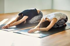 Due giovani donne che fanno la posa del bambino di asana di yoga Fotografia Stock