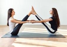 Due giovani donne che fanno posa della barca del compagno di asana di yoga fotografia stock