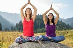 Due giovani donne che fanno yoga su una roccia Immagine Stock