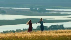 Due giovani donne che filano armi stese sul campo nel giorno soleggiato Sui precedenti del lago video d archivio