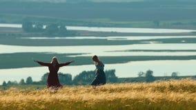 Due giovani donne che filano sul campo del weat nel giorno di calore Sui precedenti del lago stock footage
