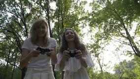 Due giovani donne che giocano i video giochi all'aperto con la leva di comando della console del gamer - stock footage