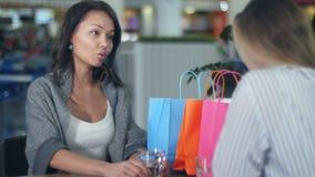 Due giovani donne che hanno discussione del qualcosa che si siede in caffè in centro commerciale video d archivio
