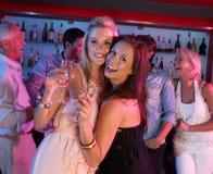 Due giovani donne che hanno divertimento in barra occupata Fotografie Stock