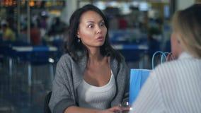 Due giovani donne che hanno pausa caffè dopo la compera in centro commerciale archivi video