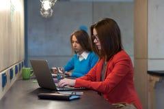 Due giovani donne che lavorano ai computer al contatore di legno di Antivari Immagini Stock Libere da Diritti