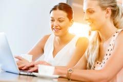 Due giovani donne che lavorano insieme al computer portatile Immagine Stock