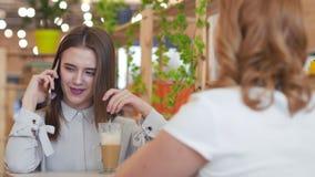 Due giovani donne che parlano e che bevono caffè che si siede in caffè archivi video