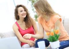 Due giovani donne che parlano e che si siedono al tavolino da salotto Immagini Stock Libere da Diritti