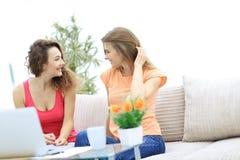 Due giovani donne che parlano e che si siedono al tavolino da salotto Fotografia Stock
