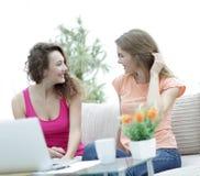 Due giovani donne che parlano e che si siedono al tavolino da salotto Immagini Stock