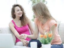 Due giovani donne che parlano e che si siedono al tavolino da salotto Fotografie Stock