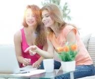 Due giovani donne che parlano e che si siedono al tavolino da salotto Fotografia Stock Libera da Diritti