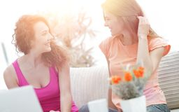 Due giovani donne che parlano e che si siedono al tavolino da salotto Immagine Stock Libera da Diritti