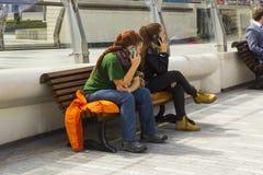 Due giovani donne che per mezzo dei loro telefoni cellulari mentre rilassandosi sulla riva al fiume Lagan del ` s di Belfast Fotografie Stock