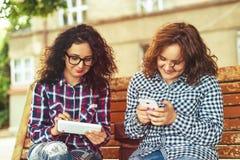 Due giovani donne che per mezzo del computer e del telefono cellulare della compressa all'aperto Fotografie Stock