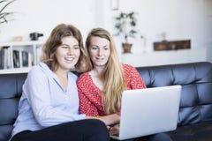 Due giovani donne che per mezzo del computer mentre sedendosi sullo strato immagini stock libere da diritti