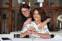 Due giovani donne che per mezzo dello smartphone dalla tavola Fotografia Stock Libera da Diritti