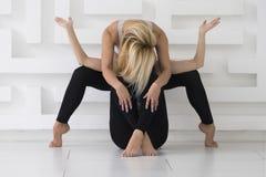 Due giovani donne che praticano l'equilibrio di yoga di acro posano, fondo del whate, tiro dello studio fotografie stock libere da diritti