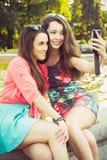 Due giovani donne che prendono un selfie all'aperto Fotografia Stock