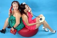 Due giovani donne che rivolgono ai telefoni su fondo blu Immagini Stock